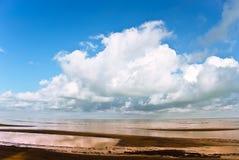 Spiaggia sotto il cielo blu nuvoloso Fotografie Stock Libere da Diritti