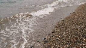 Spiaggia, spuma su un Pebble Beach, chiara acqua, tempo nuvoloso stock footage