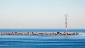 Spiaggia stretta con una città ed antenna alta all'estremità Fotografia Stock Libera da Diritti