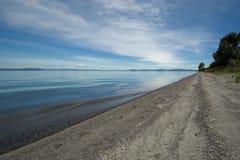 Spiaggia sul lago Taupo, isola del nord, Nuova Zelanda Fotografia Stock