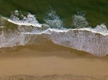 Spiaggia sulla vista superiore del fuco aereo con le onde di oceano che raggiungono riva fotografia stock libera da diritti