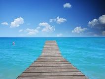 Spiaggia tropicale - acqua blu con il pavimento di legno fotografia stock