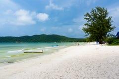 Spiaggia tropicale con l'acqua pulita del turchese, il cielo blu, la sabbia bianca e la barca nella distanza fotografia stock