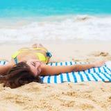 Spiaggia tropicale di menzogne della giovane bella donna di abbronzatura Fotografie Stock Libere da Diritti