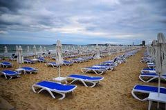 Spiaggia vuota vuota con gli ombrelli di spiaggia piegati, sedia di spiaggia blu fotografia stock
