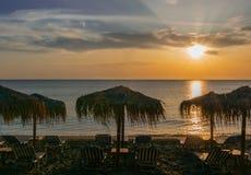 Spiaggia vuota con gli ombrelli e le chaise-lounge ricoperti di paglia del sole nelle mattine di estate fotografia stock libera da diritti