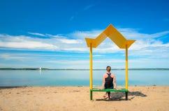 Spiaggia vuota con un banco con un baldacchino sulla costa Fotografia Stock Libera da Diritti