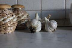 Spicchi d'aglio bianchi sul tavolo da cucina con la parete piastrellata della ceramica Immagine Stock Libera da Diritti