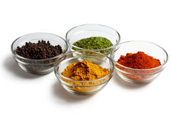 Spice assortment. Of pepper, curry, herbs and chili in glass bowls over white background Stock Photo