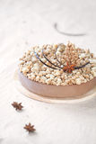 Spice Chocolate Mousse Cake with Crumble. And star anise, on a wooden plate and light background Stock Images