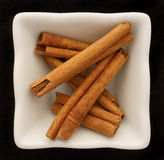 Spice cinnamon in a ceramic bowl. Isolated on black Stock Photo