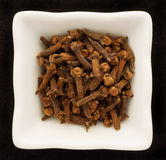 Spice cloves in a ceramic bowl. Isolated on black Royalty Free Stock Photos
