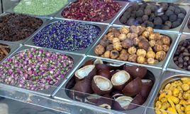 Spice and dried herb counter on the old market, Dubai, UAE. Rose, dried lemon, star anise, mint, coconut halves and hibiscus. Photo through glass. Selective royalty free stock photo
