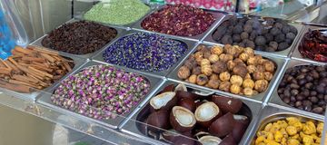 Spice and dried herb counter on the old market, Dubai, UAE. Rose, dried lemon, star anise, mint, coconut halves and hibiscus. Photo through glass. Selective royalty free stock photography