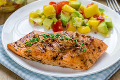 Spice grilled salmon with mango-avocado salsa Stock Images