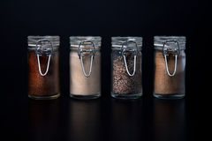 Spice Jars. Four glass spice jars lined up in a row against a black background Royalty Free Stock Photos