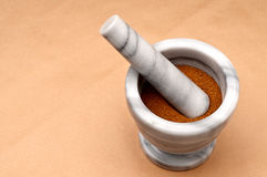 Spice in a mortar and pestle on brown. Horizontal close up of spice in a mortar and pestle on brown Royalty Free Stock Images