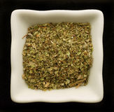 Spice oregano in a ceramic bowl. Isolated on black Royalty Free Stock Images