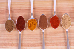 Spice Row - Landscape. Six different ground spice powders in silver spoons on a wooden background Stock Photography