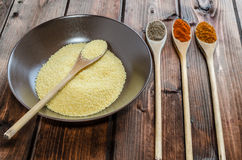 Spice on spoon with bowl of couscous Stock Photos