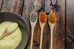 Spice on spoon with bowl of couscous Royalty Free Stock Photos