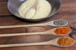 Spice on spoon with bowl of couscous royalty free stock photo