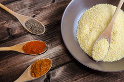 Spice on spoon with bowl of couscous Royalty Free Stock Images