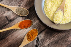 Spice on spoon with bowl of couscous Royalty Free Stock Photography