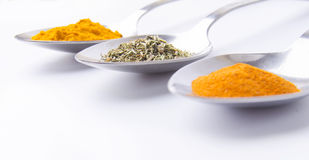 Spice spoons. Three spoons with spices on a white background. Focus on the middle spoon Stock Images