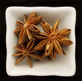Spice star anise in a ceramic bowl. Isolated on black Royalty Free Stock Photos