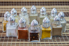 Spice. Twelve dispensing containers with metal lid containing colorful spices Stock Photography
