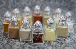 Spice. Twelve dispensing containers with metal lid containing colorful spices Royalty Free Stock Photography