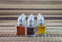 Spice. Twelve dispensing containers with metal lid containing colorful spices Royalty Free Stock Images