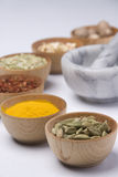 Spice it up. Bowls of dried and ground spices with mortar and pestle Stock Photography