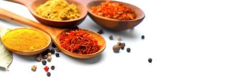 spice Várias especiarias em colheres de madeira sobre o branco Caril, açafrão, cúrcuma, canela Foto de Stock