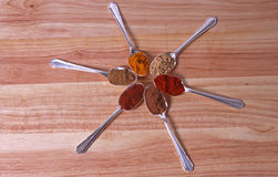 Spice Wheel. Six different ground spice powders in silver spoons on a wooden background Stock Photos