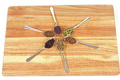 Spice Wheel. Six different whole spice seeds in silver spoons on a wooden chopping board against a white background Royalty Free Stock Image