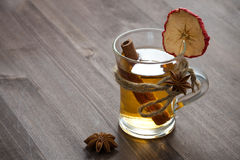 Spiced apple cider in glass mug on a wooden table Royalty Free Stock Images