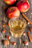 Spiced apple cider and spices on a wooden table, close-up. Vertical Royalty Free Stock Image