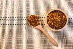 Spiced cayenne pepper in wooden bowl. Top view Stock Photo
