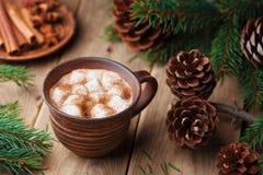 Spiced gorący kakao z marshmallows na nieociosanym drewnianym stole dekorował sosny szyszkowego i jedlinowego drzewa obrazy stock