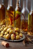 Spiced green olives and bottles with olive oil . Stock Photos