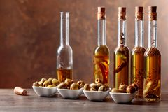 Spiced green olives and bottles with olive oil . Stock Photography