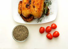 Spiced grilled chicken. Top view of grilled chicken with pepper, cherry tomatoes and herbs. isolated on white stock photos