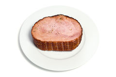 Spiced Ham. A cooked ham on a white plate with spices on top, isolated Royalty Free Stock Image