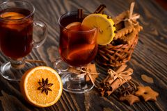 Spiced Homemade Mulled Wine with Orange and Cinnamon. On a dark wooden background stock photos