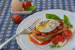 Spiced poached egg on sandwich near fork on white plate. And ingredients Royalty Free Stock Image