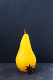 Spiced Poached Saffron Pear. Single pear poached in sugar and saffron syrup spiced with star anise on a gray slate with dark textured background Royalty Free Stock Photos