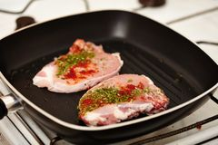 Spiced raw pork chops in the frying pan Stock Images