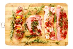 Spiced raw pork meat. Closeup of spiced  raw pork meat on a wooden board, isolated on white background Stock Photo